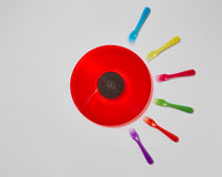 Colorful plastic forks around red vinyl record on a light gray background.
