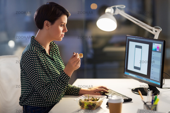 designer eating and working at night office