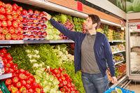 Junger Mann kauft frisches bio Gemüse