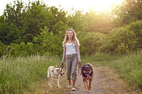 Happy young woman walking wiht her dogs