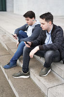 two mobile phone addicted male teenagers looking at smartphone