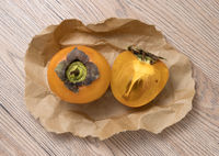 Delicious ripe persimmon fruit on craft paper, on wooden background.