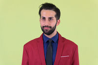 Face of young bearded Persian businessman in suit thinking