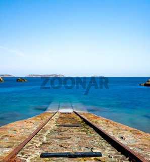 old stone boat ramp for rescue ships leading into a calm blue ocean on the coast of Brittany