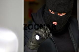 Einbrecher bei Einbruch nachts mit Taschenlampe