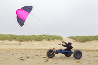 Teenage boy drives buggy with kite on beach