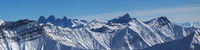 Panoramic view of snowy mountains at sun winter day