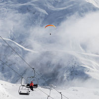Chairlift and paraplane in fog on ski resort