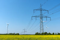 Overhead power lines in a field of blooming oilseed rape seen in rural Germany