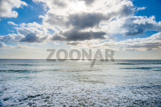 Seascape with silver sunlight reflection, sky and clouds