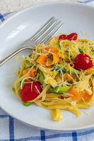 Homemade pasta with strips of zucchini and carrots.