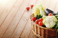 Organic vegetable food ingredients in the basket on wood background