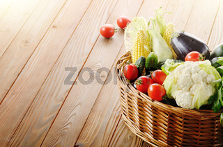 Organic vegetable food ingredients in the basket on wood background