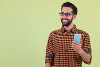 Happy young bearded Persian hipster man thinking while using phone
