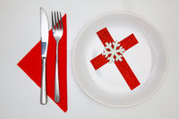 White plate and red Christmas decoration.
