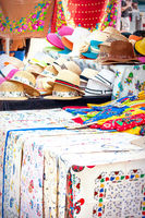 Booth with hats, embroidered tablecloths and other textiles as a souvenir from Portugal
