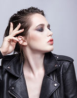 Portrait of female in black leather jacket.Woman with unusual beauty evening makeup and violet - black shadows make-up.