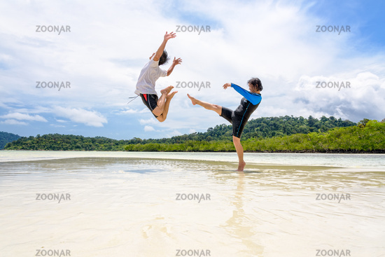 Couple play fun woman show kicking a man on the beach