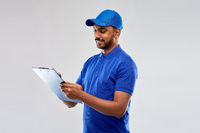 happy indian delivery man with clipboard in blue