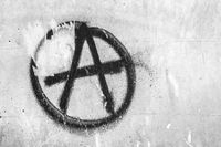 Symbol of anarchy painted on the peeling old wall