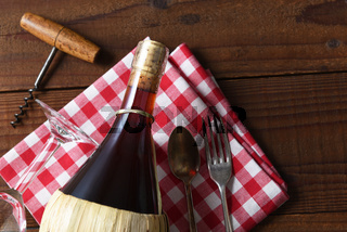 A basket bottle of Chianti wine on a red and white checked napkin with Corkscrew fork and spoon