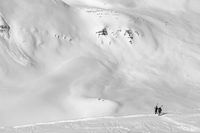 Two skiers with skis on his shoulder and off-piste slope