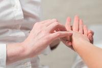 Professional female masseur giving reflexology massage to woman palm