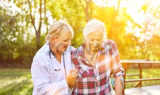 Alte Frau mit Physiotherapeutin bei Bewegungstherapie