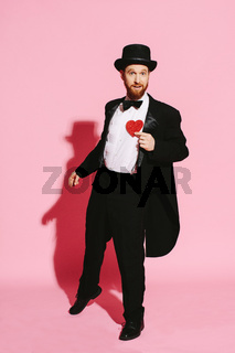 dancing man in a tuxedo and top hat holding a red heart