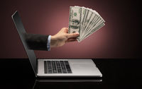 Hand with money  coming out of a laptop