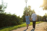 couple walking through grassy and green road