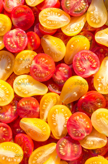 Fresh halves of Mexican cherry tomatoes. Sliced yellow and red cherry tomatoes.Background of many co