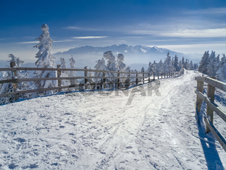 Winter snow wonderland landscape. Christmas scenic background with mountains, trees and road covered in snow. View of Bucegi mountains, Brasov, Romania.