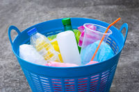 Plastic bottles in blue waste basket on cement floor.