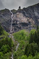 high waterfall plummets off a rock and grass cliff in the Swiss Alps