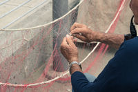 Old man reparing fishing net