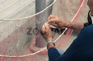 Old man reparing fishing net