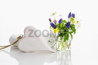 Weiße Handtücher mit Herz neben einem kleinen Strauss frischer Blumen.