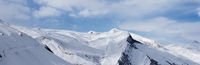 Panorama of snowy winter mountains and blue sky with clouds