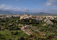 Aerial distant photo drone point of view image Campanet town hillside residential old ancient houses building exterior situated in the northeast of Majorca Island, Spain