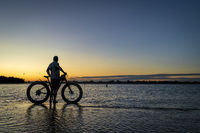 sunrise silhouette of a man with fatbike