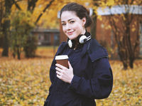 young woman with coffee to go cup and headphones in autumn