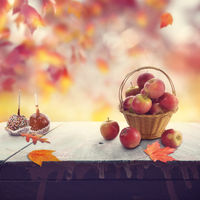 Old wooden table with apples and autumn leaves