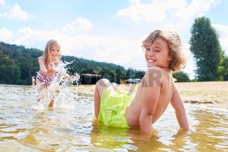 Kinder plantschen ausgelassen im See