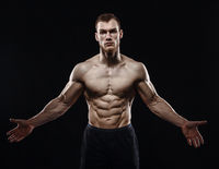 Aggressive man is a fighter, a bodybuilder on a black