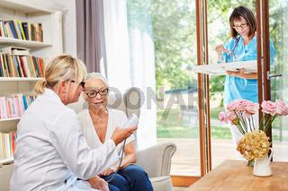 Ärztin kontrolliert Blutdruck bei einer Seniorin