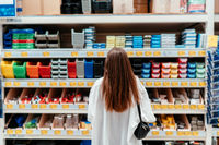 Woman chooses plastic boxes of different colors for the workshop