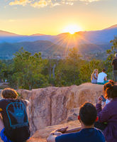 People watching sunset over mountains
