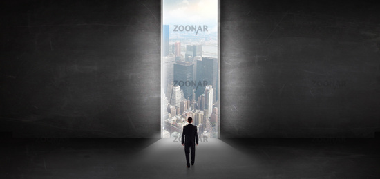 Businessman looking to a cityscape from a dark empty room