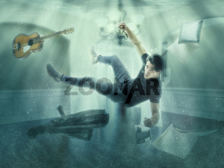Man floating underwater in room having dream